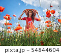 Dreamy woman in red dress and a big red striped hat in beautiful herb flowering poppy field. Vintage 54844604