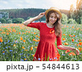 Lovely young romantic woman in straw hat on poppy flower field posing on background summer. Wearing 54844613