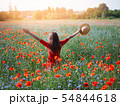 Young beautiful woman with raised arms in spring poppy field. Concept freedom and happiness summer 54844618