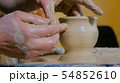 Professional potter shaping mug in pottery workshop 54852610