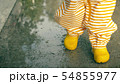 Little baby in orange striped waterproof raincoat and yellow rubber rain boots walks on puddles 54855977
