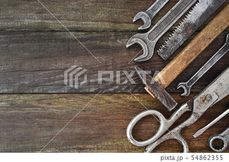 Retro vintage woodwork equipment set. Hammer scissors screwdriver on brown texture wooden planks 54862355