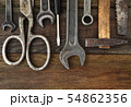 Retro vintage woodwork equipment set. Hammer scissors screwdriver on brown texture wooden planks 54862356