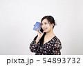 白い背景の前でスマホで会話をしている笑顔の若い女性 54893732