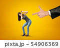Man's hand in suit pointing fingergun at miniatured pretty girl in casual clothes, who is protecting 54906369