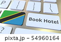 BOOK HOTEL text and flag of Tanzania on the buttons on the computer keyboard. Travel related 54960164