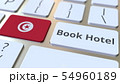 BOOK HOTEL text and flag of Tunisia on the buttons on the computer keyboard. Travel related 54960189