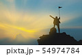 silhouette of man on mountain top over sky and sun 54974784
