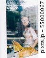 Pretty young woman drinking coffee stroking doggy sitting on window sill in cafe 55000067
