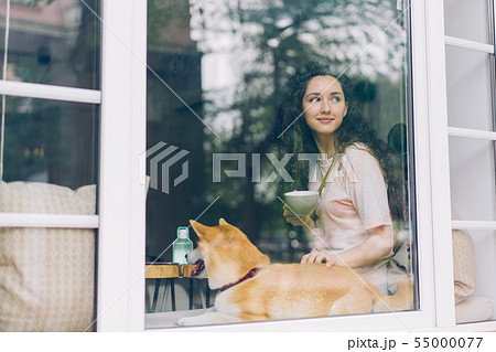 Cute girl relaxing in cafe with cup of coffee petting cute pedigree dog 55000077