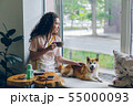Student stroking shiba inu dog sitting in cafe on window sill with cup of tea 55000093