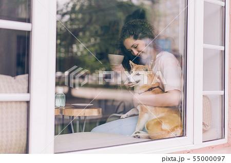 Beautiful young woman drinking tea in cafe hugging cute dog on window sill 55000097