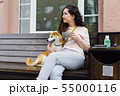 Pretty girl sitting in street cafe with cup of tea and shiba inu dog smiling 55000116
