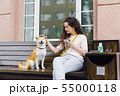 Smiling lady stroking beautiful dog and holding cup of coffee in street cafe 55000118