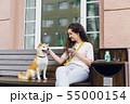 Happy young woman drinking tea outdoors in cafe stroking cute shiba inu puppy 55000154