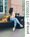 Beautiful curly-haired girl sitting in street cafe with cute dog smiling 55000155