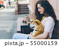 Young woman using smartphone enjoying social media with dog in street cafe 55000159