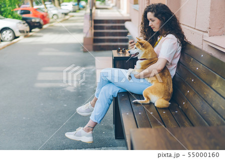 Smiling girl using smartphone hugging adorable shiba inu dog outdoors in cafe 55000160