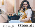 Beautiful lady speaking on mobile phone hugging shiba inu dog outdoors in cafe 55000161