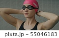 Woman wearing goggles preparing to swim 55046183