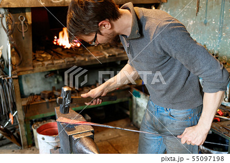 Blacksmith forging red-hot metal with hammer. 55097198