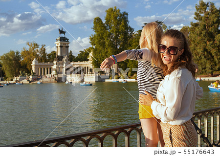 happy mother and child tourists at Park del Retiro rejoicing 55176643