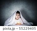 Little child with flashlight hiding under blanket 55229405