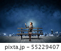 Young woman holding open book on bench 55229407