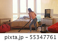 Young woman is hoovering the floor at home using modern vacuum cleaner and listening to music with 55347761