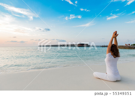 woman practicing yoga lotus pose on the beachの写真素材