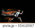 Young handball player against dark studio background in mixed light 55410567