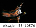 Young handball player against dark studio background in mixed light 55410570