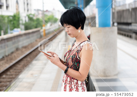 mature traveling woman waiting and using a 55473052
