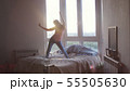 Happy young woman jumps and dances on bed in luxury apartment during beautiful sunrise with lens 55505630