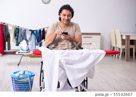 Young man in wheel-chair doing ironing at home 55532607