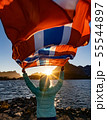 Woman waving the flag of Norway at sunset 55544897