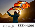 Woman waving the flag of Norway at sunset 55544899