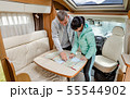 Couples in RV Camper looking at the local map for 55544902
