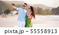 Happy couple taking a selfie photo on white beach. 55558913