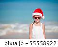 Adorable little girl in Santa hat on tropical beach 55558922