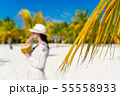 Young woman drinking coconut milk on hot day on the beach. Closeup palm leaves 55558933