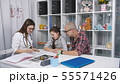 4K Friendly doctor talking to father and child patient in office. 55571426