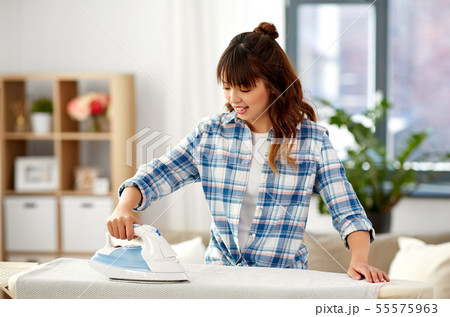 asian woman ironing bed linen at home 55575963