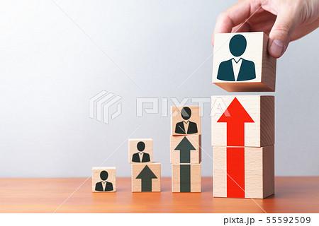 ビジネスにおける個人の成長。上昇する矢印と人のアイコン。テーブルで積み木を積み上げる手のアップ。 55592509
