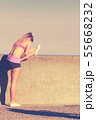Woman doing sports exercises outdoors by seaside 55668232
