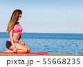 Woman in sportswear sitting on dyke by sea 55668235