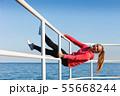 Woman fool around sitting on handrail near sea 55668244