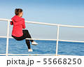 Woman sitting on pier looking at horizon outdoors 55668250