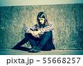 Man long haired sitting alone sad on grunge wall 55668257