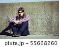 Man long haired sitting alone sad on grunge wall 55668260